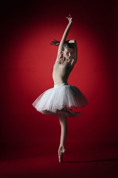 Ballerina. Young graceful female ballet dancer dancing at red studioskill. Beauty of classic ballet.
