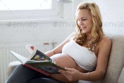 Pregnant woman resting and reading book on sofa