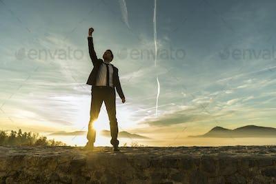 Triumphant businessman greeting a new day