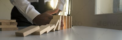 Wide panorama of a businessman stopping the domino effect