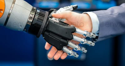 Hand of a businessman shaking hands with a droid robot. The conc