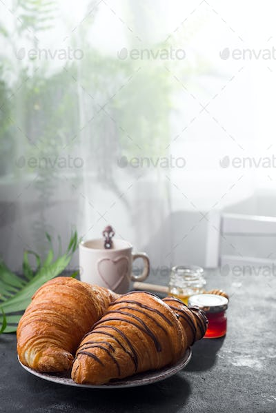 breakfast freshly baked croissant decorated with jam and chocolate on wooden table in a kitchen