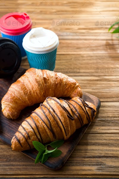 cups of coffee and two croissants on the street in Croissant Cafe. Inscripton on cup