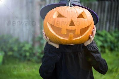 Little girl holding spooky funny pumpkin