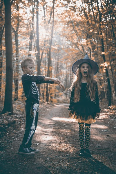 Kids as zombie at halloween walking in forest