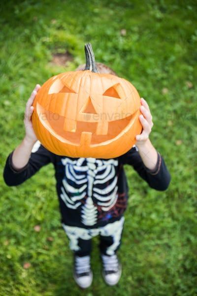 Boy in skeleton costume holding pupmkin