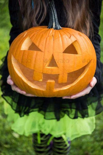 Girl in halloween costume holding spooky pumpkin