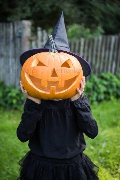 Funny girl with halloween pumpki in garden