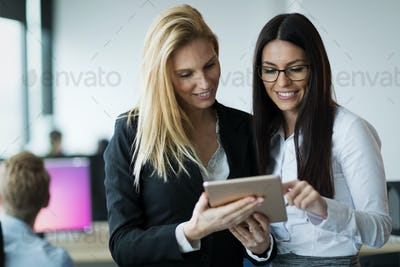 Portrait of two attractive businesswomen using tablet in office