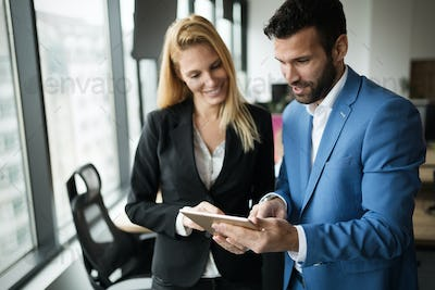 Businesspeople discussing while using digital tablet in office