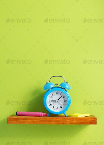 alarm clock on shelf at wall background