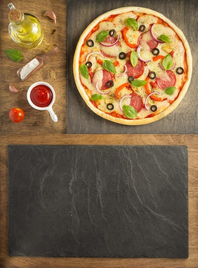 pizza and food ingredients at wooden table