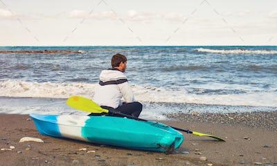 man sitting on kayak at sea beach