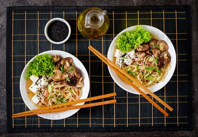 Vegan noodle soup with tofu cheese, shiitake mushrooms and lettuce