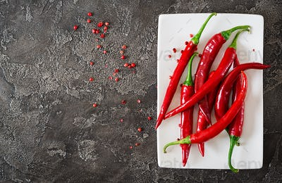 Red hot chili peppers in plate on grey table. Top view