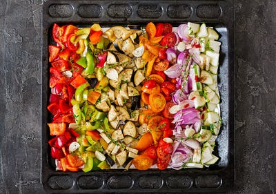 Sliced vegetables on a baking tray prepared for baking.