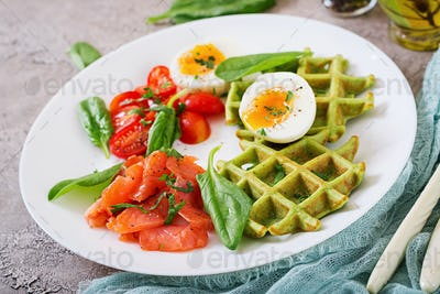 Savory waffles with spinach and egg, tomato, salmon in white plate. Tasty food.