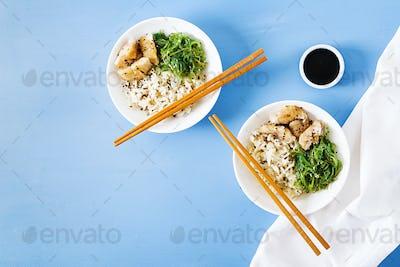 Bowl of rice, boiled white fish and wakame chuka or seaweed salad.