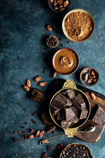 Dark chocolate pieces crushed and cocoa beans. Chocolate background