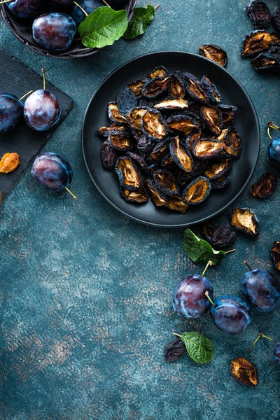 Dried prune and fresh plums with leaves