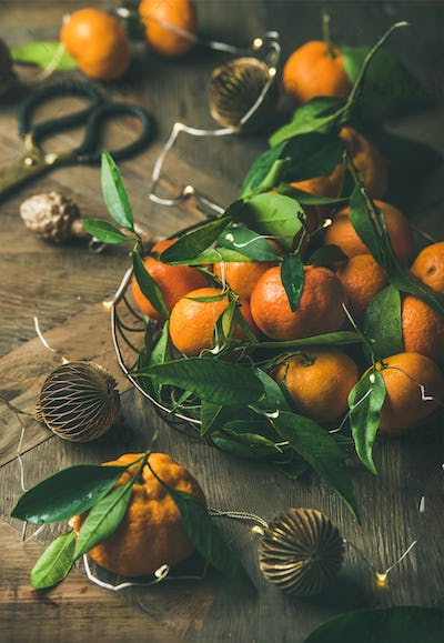 Fresh tangerines with leaves and decoration toys on Christmas table
