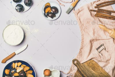 Baking ingredients and tools over pastel lilac background