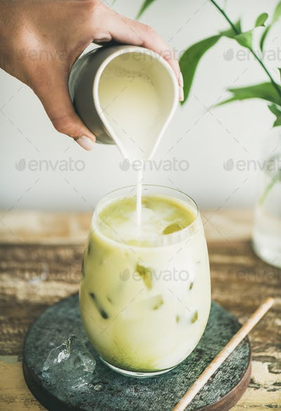 Iced matcha latte drink with milk pouring from pitcher, close-up