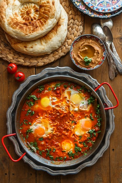 Tasty Breakfast Shakshuka in a Iron Pan. Fried eggs with tomatoes, Healthy Food.