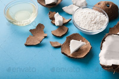 Plate with coconut flour and water on blue background
