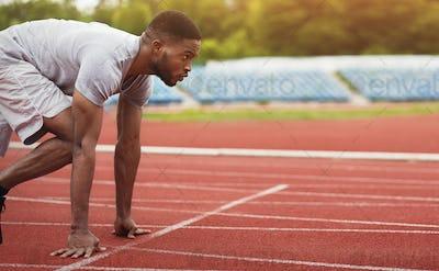 African-american male sportsman ready to run on stadium track