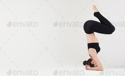 Slim woman doing advanced yoga pose on white background