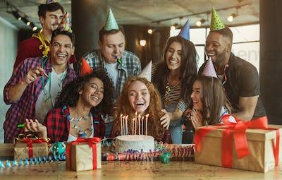Friends presenting birthday cake to girl