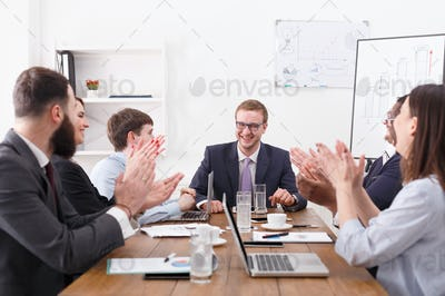 Business team meeting at white office siterior. Workers clapping hands cheering successful reporter