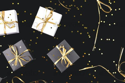Black and white gift boxes with gold ribbon on shine background.