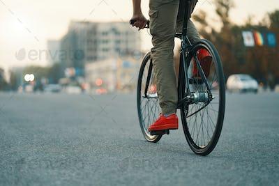 Closeup of casual man legs riding classic bike on city road
