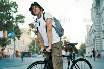 A man riding a bike in an old European city outdoors