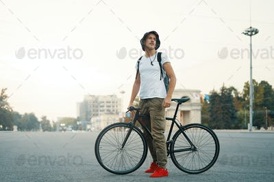 Portrait of young man walking with thoughtfully classic bicycle