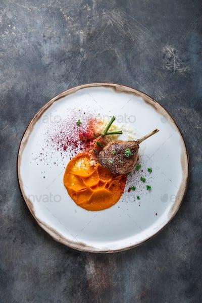 Duck leg confit with batat puree, carrots and couscous, restaurant meal, copy space