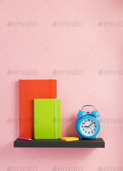 notepad and alarm clock on shelf at wall background