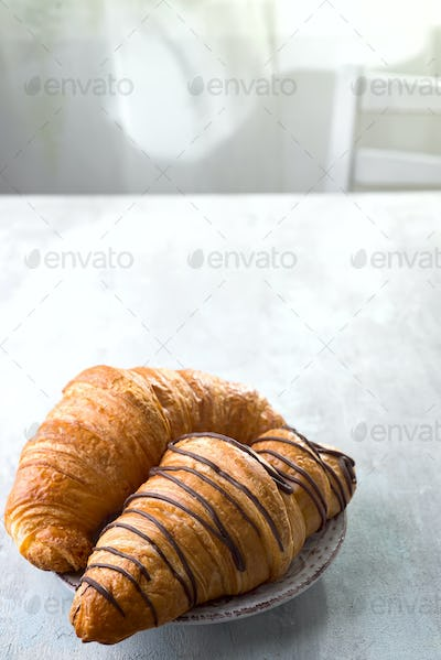 freshly baked croissant decorated with chocolate sauce isolated on a gray slate background