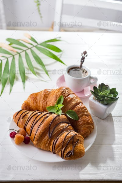 Continental breakfast freshly baked croissant decorated with jam and chocolate on wooden table
