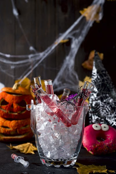 cocktail in glass tubes in an ice bucket with black spiders and a spider web in the background