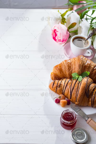 breakfast freshly baked croissant decorated with jam and chocolate, flowers on wooden table