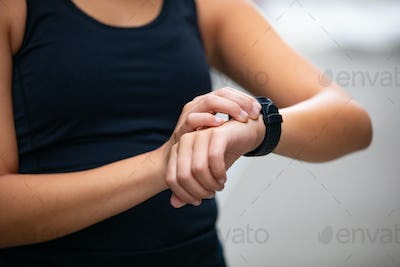 Close-up of woman using fitness smart watch device before running