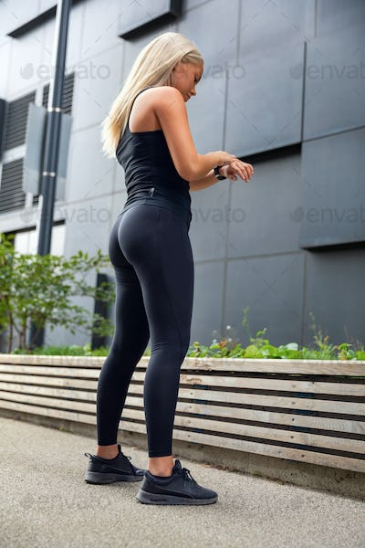Urban woman using fitness smart watch device before running