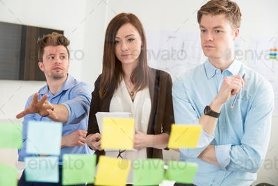 Businesswoman Looking At Strategies On Adhesive Notes By Colleag