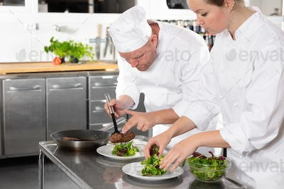 Two professional chefs prepares steak dish at gourmet restaurant