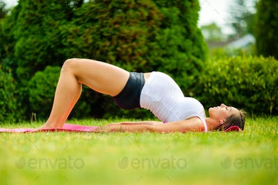 Pregnant Woman Practicing Bridge Pose On Grass