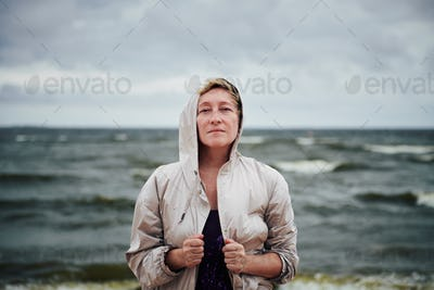 Adult woman in jacket standing near sea