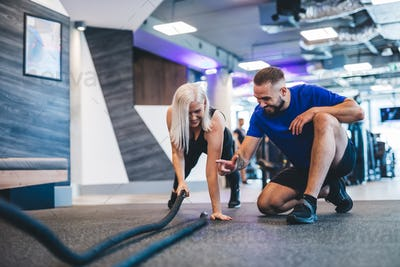 Gym instructor and a woman exercising at the gym.